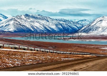 The highway winds along the Alaska Pipeline on Alaska's North Slope - stock photo