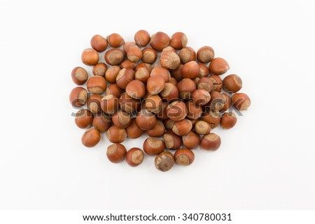the hill of hazelnuts in a shell lies on a white background
