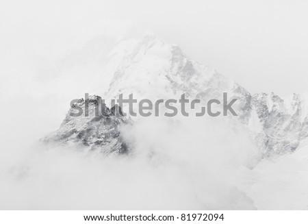 The himalayan peak near Mt. Everest in the fog - stock photo