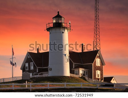 The Historic And Beautiful Nobska Point Lighthouse In Early Morning Light With A Deep Red Sky As Background, Woods Hole, Cape Cod, Massachusetts, USA - stock photo