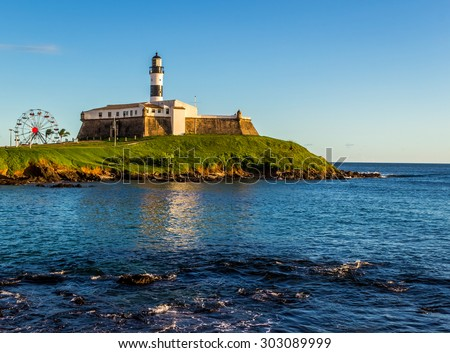 The historic architecture of Salvador in Bahia, Brazil showcasing the Farol da Barra Lighthouse at Bahia de Todos os Santos Bay on a sunny summer day. - stock photo
