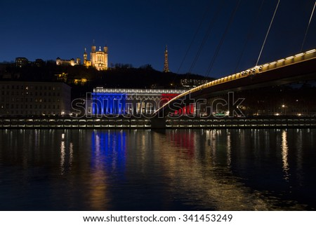 The historic courthouse of Lyon with the colors of France flag with  Basilica of Fourviere over the soane in background at sunset. - stock photo