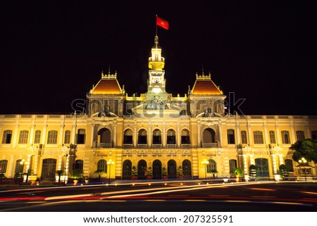 The historic Peoples' Committee Building in Ho Chi Ming Square on the 100 years anniversary of Ho Chi Minh's departure for Europe. Ho Chi MInh City (Saigon) Vietnam. Night shot. - stock photo