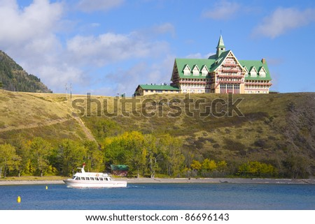 The historic Prince of Wales Hotel sits on a bluff overlooking Waterton Lake in Waterton Lakes National Park. - stock photo