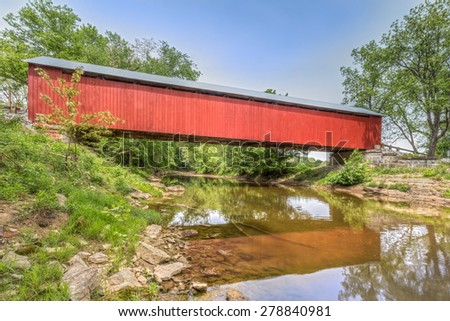 The historic red James Covered Bridge crosses Big Graham Creek in rural Jennings County, Indiana. - stock photo