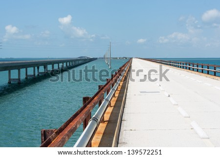 The historic Seven Mile bridge was built by Henry Flagler as part of the Overseas Railroad to Key West. The new seven mile bridge can be seen on the left running alongside the old bridge. - stock photo