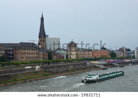 The historical center of Dusseldorf (Germany) and a barge on the Rhine - stock photo