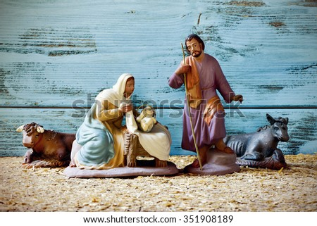 the holy family, Child Jesus, the Virgin Mary and Saint Joseph, and the donkey and the ox in a rustic nativity scene - stock photo