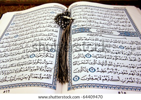The holy Koran opened with a rosary on it - stock photo