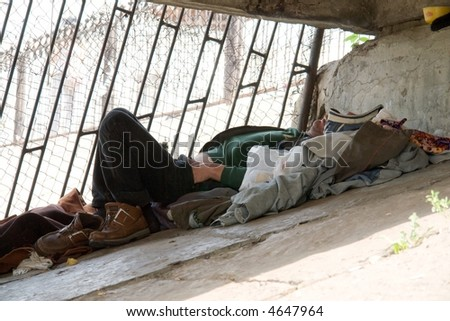 The homeless person sleeps under the bridge - stock photo