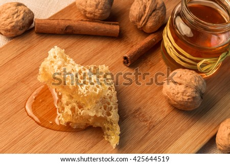 The honey, walnuts and pods of cinnamon lying on a chopping board from a bamboo.