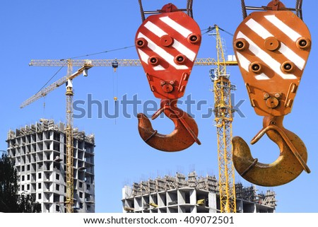 The hook of the elevating crane on a background of construction - stock photo