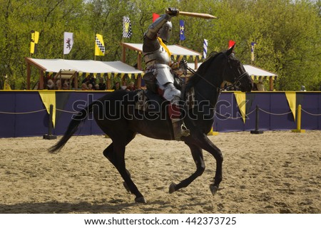 The horse knight in an armour and in a helmet with a sword in a hand. St.George knightly tournament. Moscow on May 1, 2016