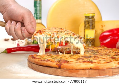 The hot prepared pizza with sticky cheese on a shovel from the cook - stock photo