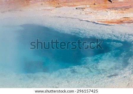 The hot steamy thermal water in Silex Spring pool reflecting the blue rays of the sun in Yellowstone National Park. - stock photo