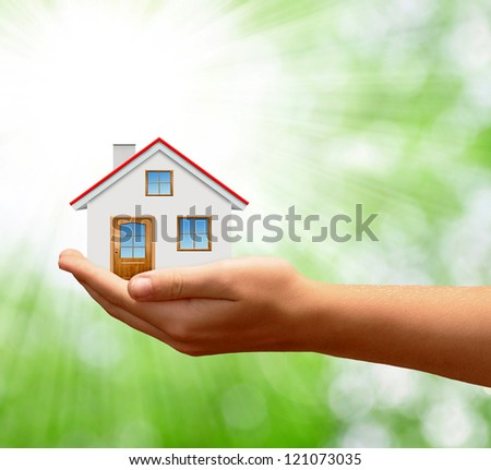 The house in hands on green natural backgorund - stock photo