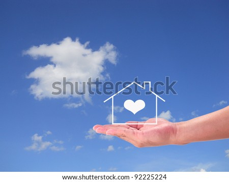 The House in the hands against the blue sky - stock photo