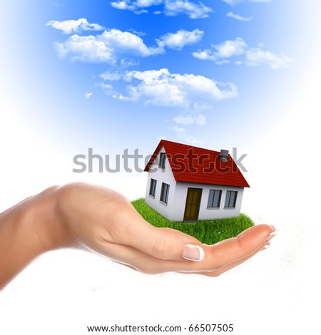 The House in the hands against the blue sky as a symbol of the real estate business. - stock photo