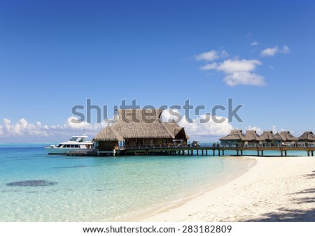the house on piles and yachts in a bay - stock photo