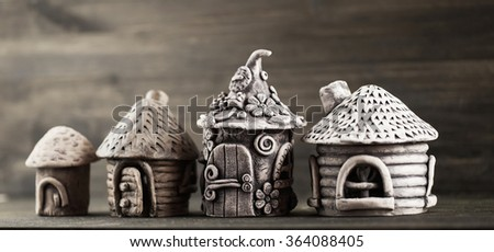 The houses made of mud, standing on a wooden board. Fairy houses for dwarfs wizards. - stock photo