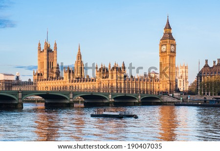 The Houses of Parliament and the Big Ben in London seen from the Queen's Walk riverfront at dawn - stock photo