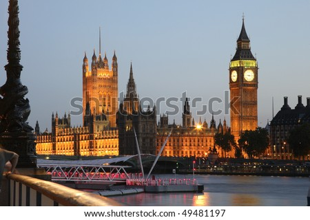The Houses of Parliament at Westminster Palace in London, seen from across the Thames River at dusk. Horizontal shot. - stock photo