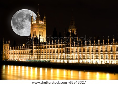 The Houses of Parliament in London at night with a bright full moon - stock photo