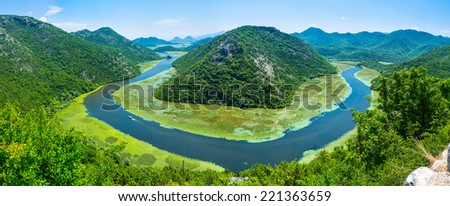 The huge bend of the Crnojevica river, surrounded by the lush forest, Rijeka Crnojevica, Montenegro. - stock photo