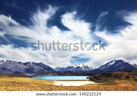 The huge deserted National Park Perito Moreno in Patagonia, Argentina. Strong wind turns the clouds in a valley surrounded by snow-capped mountains