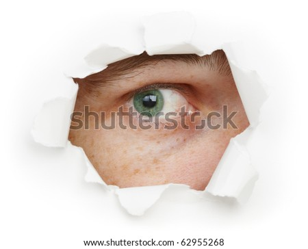 The human eye is watching us through a hole - stock photo