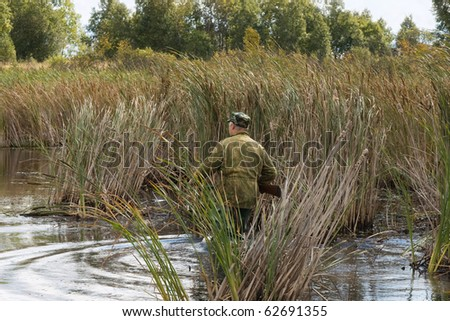 The hunter goes on lake in search of wild ducks - stock photo