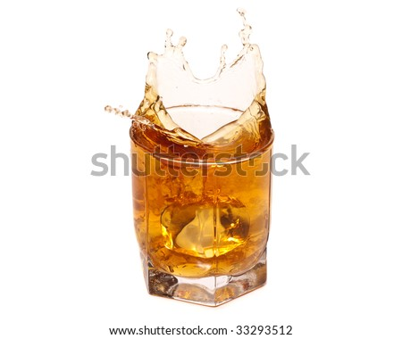 The ice cube falls in a  glass with whisky. Splashes.