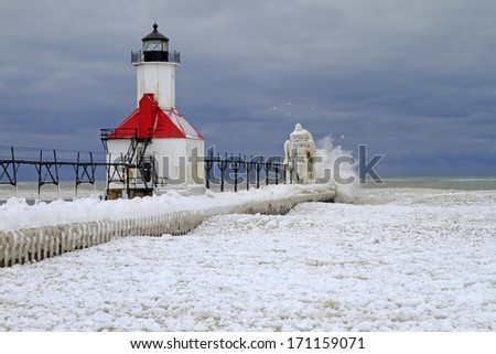 The Ice Maker - Waves crashing against the outer lighthouse at St. Joseph set the stage for an ice build-up on the pier and lighthouses during an early winter storm. - stock photo