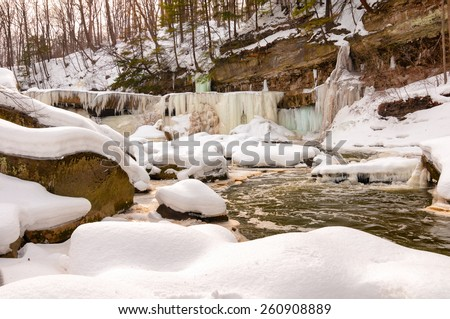 The iced-over Great Falls of Bedford Ohio seen from downstream at creekside - stock photo