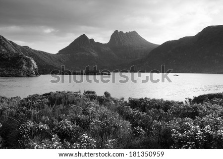 The iconic image of Tasmania, Cradle Mountain sits majestic atop the the jewel that is Dove Lake bathed in glowing sunset light in black and white - stock photo