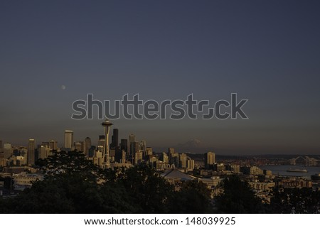 The iconic view of the Seattle skyline at sunset from Kerry Park with full moon overhead and Mount Rainier on the horizon. - stock photo
