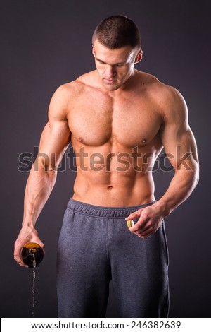 The idea of a healthy diet. Bodybuilder pours beer. Beer - not a healthy diet. Muscular guy with a beer in hand.