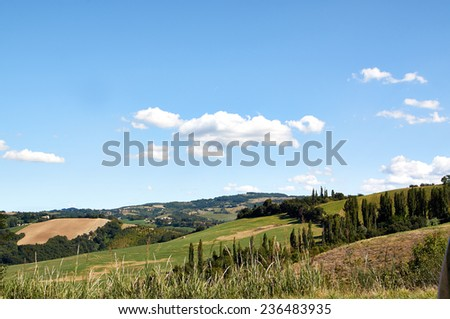The idyllic countryside of Italy. The glassy surface of fields and the blue mountains.