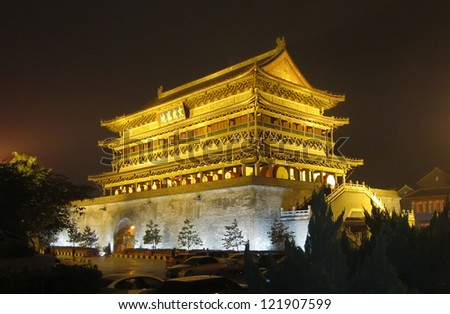 The illuminated ancient Drum Tower located at the ancient city wall by night time, Xian, Shanxi Province, China - stock photo