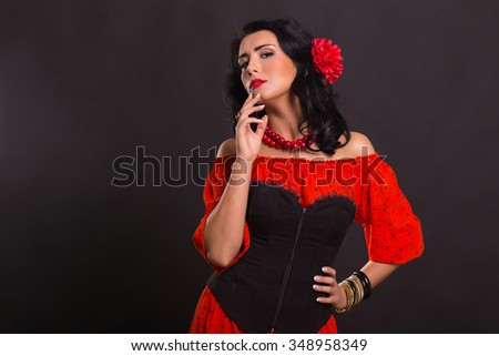 The image, chic, sexy Spaniard. Chic, sexy woman in a red dress. Portrait of gorgeous brunette in red in the studio. Emotional portrait.