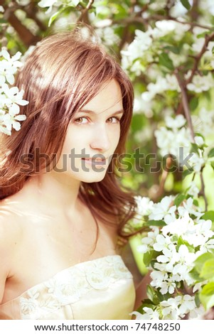 The image of a beautiful girl in the lush spring garden