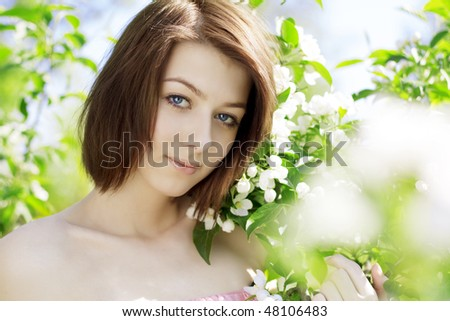 The image of a beautiful girl on a background of flowering trees
