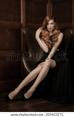 The image of a beautiful luxurious woman sitting on a leather vintage chair.