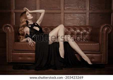 The image of a beautiful luxurious woman sitting on a leather vintage couch.