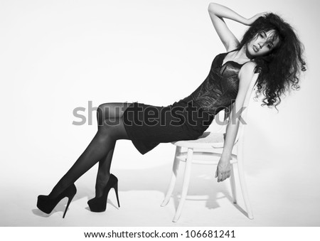 The image of a beautiful woman sitting on chair. Studio shot - stock photo