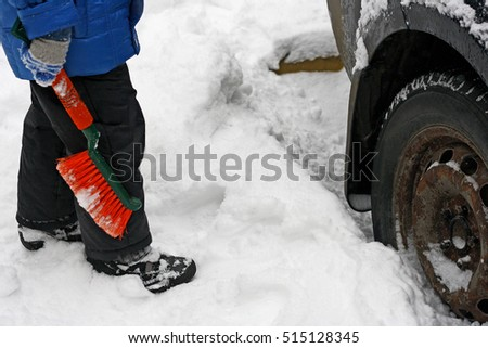The image of a child standing near the car with the old rusty wheels and holds the orange brush to clean the snow from the car.