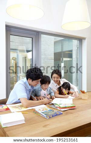 the image of a happy Asian family doing coloring  - stock photo