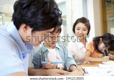 the image of a happy Asian family drawing