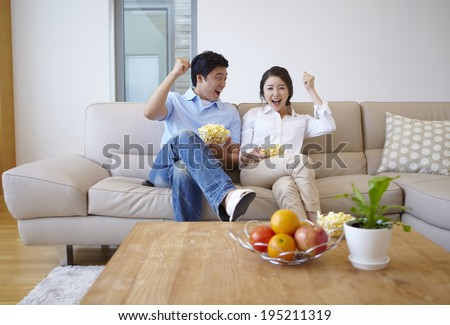 the image of a happy Asian family eating popcorn - stock photo