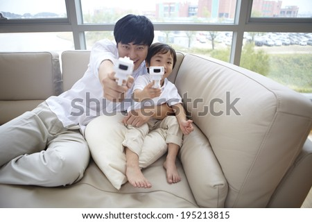 the image of a happy Asian father and son with toy guns - stock photo